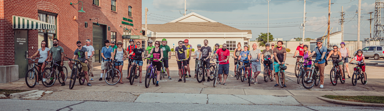 A group of bicyclists in front of Joseph Newman Innovation Center