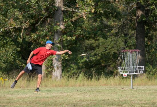 A man throws a frisbee towards a disc golf basket