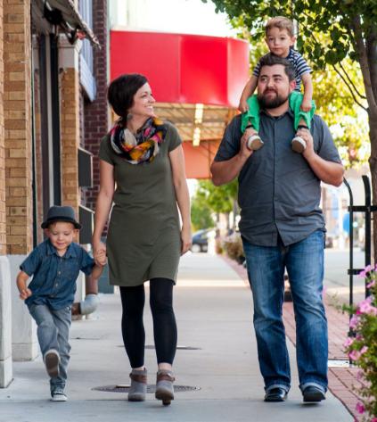 A family walks on a sidewalk in downtown Joplin