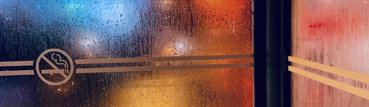 The no smoking symbol against a rain-splattered door