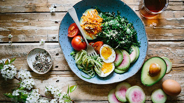 A plate of avocado, hard-boiled egg, tomato, and other diabetic-friendly foods
